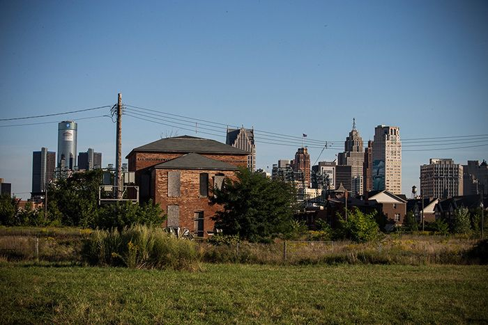 An abandoned home is seen with the Detroit skyline in the background