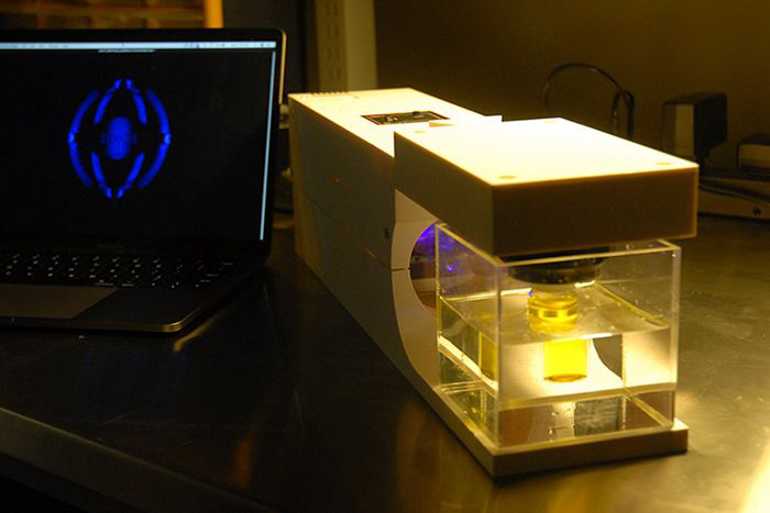 The 3D printer works by shining changing patterns of light through a rotating vial of liquid.