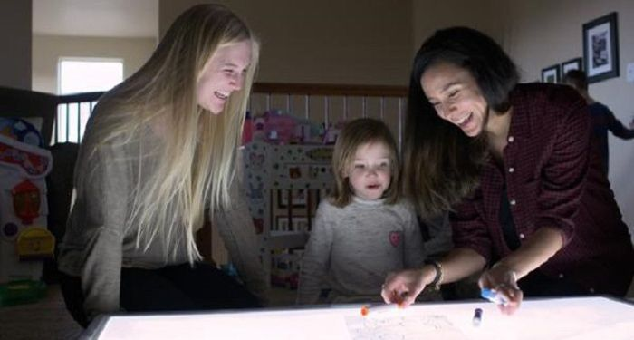 Undergraduate research associate Allie Coy (left) and CU Boulder instructor Lameese Akacem (right) play with a child over a light table.