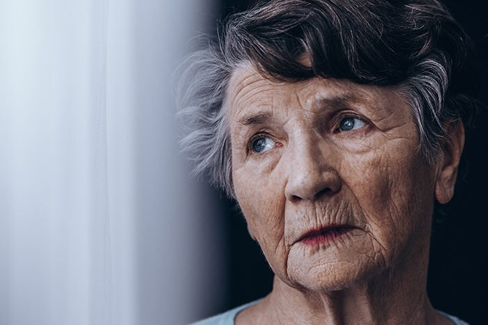 Older woman staring out a window