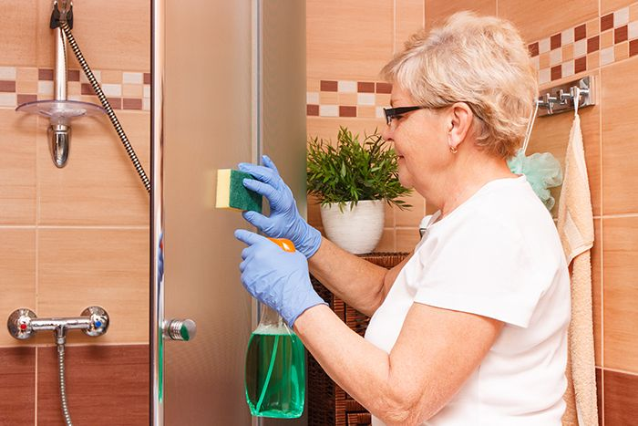 Older woman cleaning bathroom shower