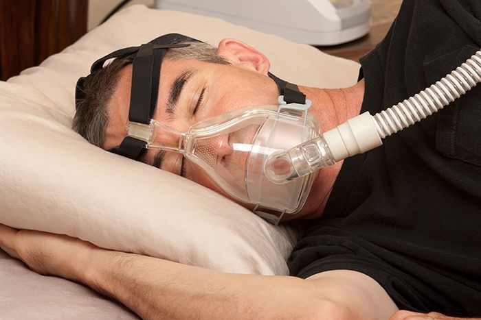 Photo of man with sleep apnea wearing cpap machine.
