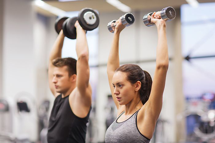 Image: Man and woman lifting weights