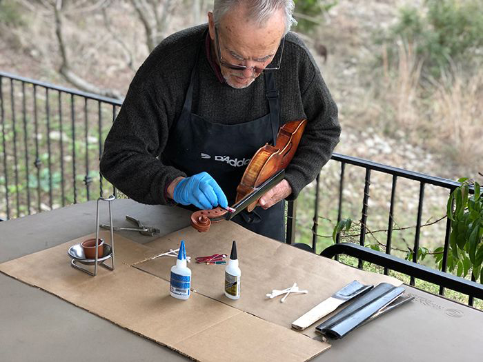 Image: Joseph Nagyvary applies glue to a violin fingerboard.