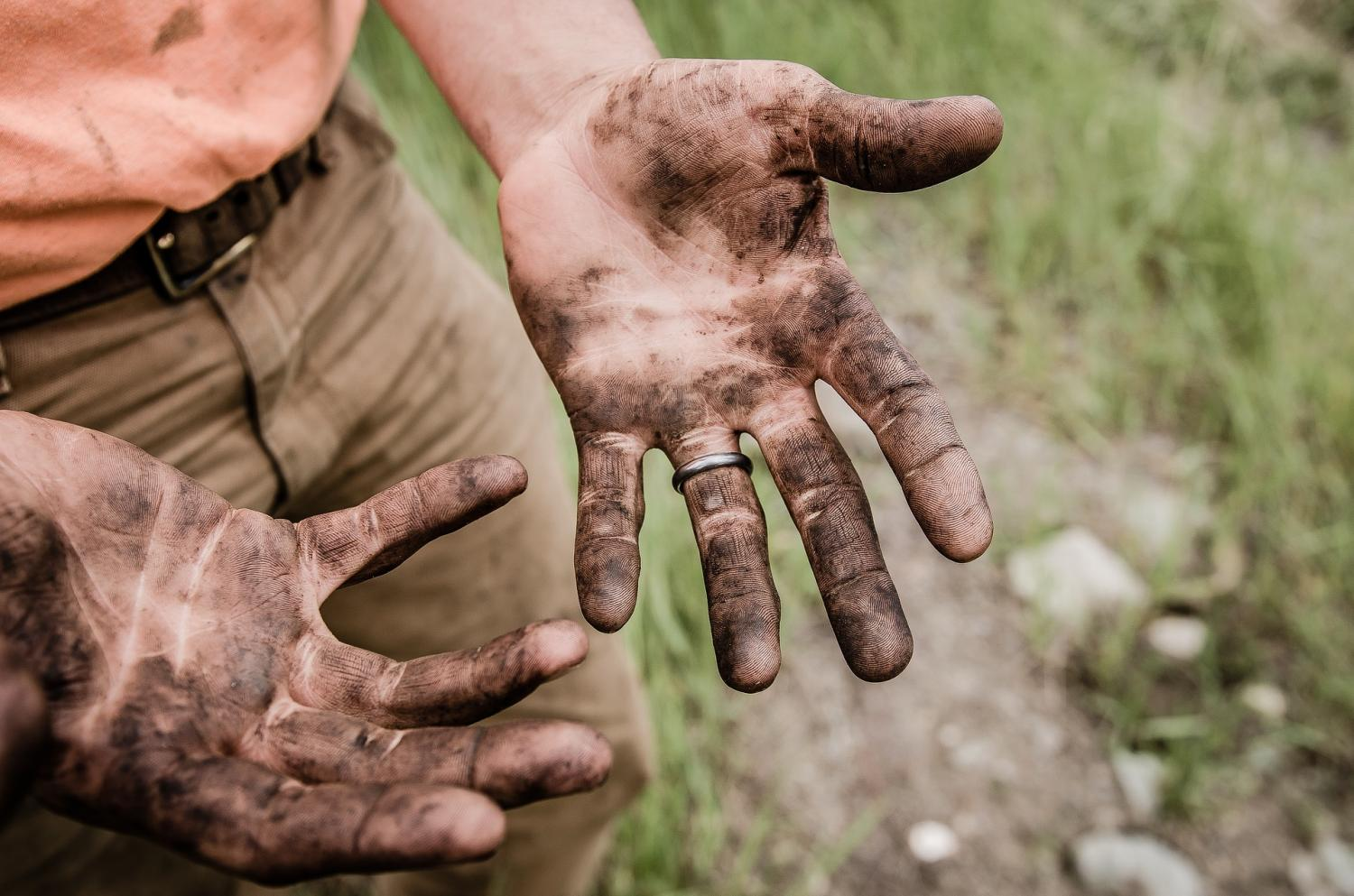A man shows off his dirty hands.