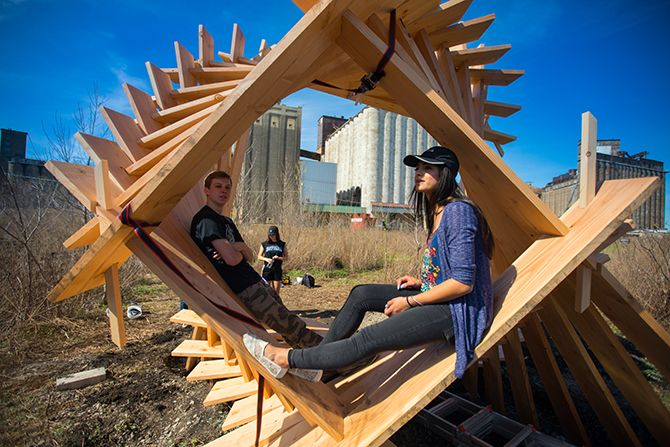 Freshman architecture students from the University at Buffalo sit inside one of the 10 structures their design studio made at Silo City.